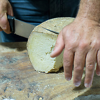 A man slices some Sardinian Cheese Bussu at Biennale del Gusto on October 28, 2013 in Venice, Italy. The Biennale del Gusto is an exhibition held over four days, dedicated to traditional food and drinks from all regions of Italy.