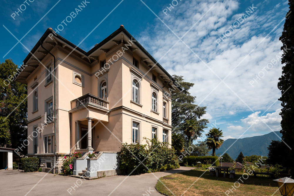 Period villa with large garden around it on a sunny summer day