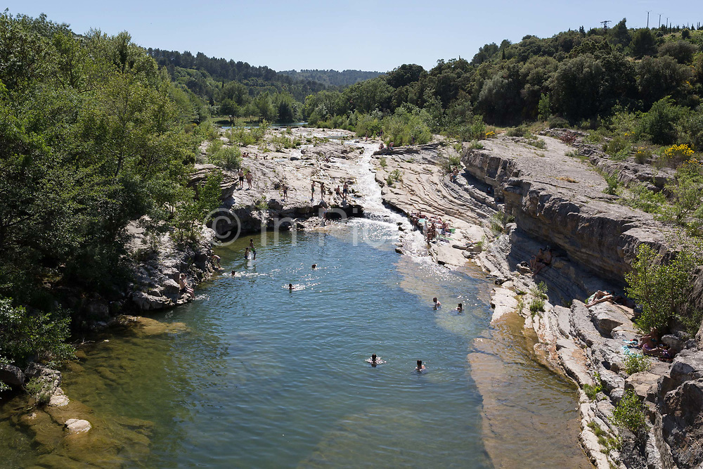 Bathers swim in the natural waters of the River Orbieu flowing through rocky gorge, on 24th May, 2017, in Ribaute, Languedoc-Rousillon, south of France.