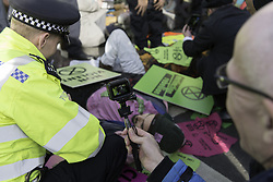 October 31, 2018 - London, Greater London, United Kingdom - Environmental activists are seen lying in the middle of the road around Parliament Square during the protest..The newly formed Extinction Rebellion group, concerned about climate change, calls for a peaceful mass civil disobedience to highlight politicians' lack of commitment and action regarding environmental issues. Activists gathered at the Parliament Square and blocked the road for two hour. The protest included speakers such as Greta Thunberg, Caroline Lucas, and George Monbiot. According to Extinction Rebellion 15 people were arrested in the protest. (Credit Image: © Andres Pantoja/SOPA Images via ZUMA Wire)