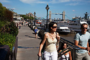 People taking a walk along the North side of the River Thames, London. Tower Bridge in the distance this is a popular walk with tourists and locals alike. You can walk all the way in to central London along the river.