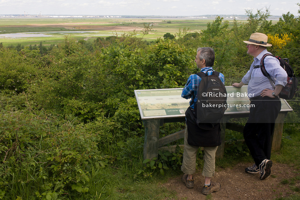Two country ramblers look across Northwood Hill's landscape below, an wildlife area near Halstow on the Kent Thames estuary marshes, potentially threatened by the future London airport.
