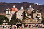 School children pass in front of the cathedral in Mitla, Mexico.