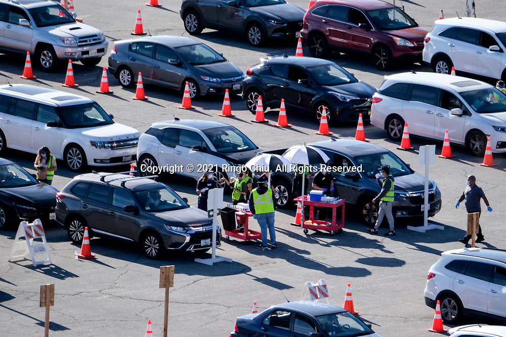Healthcare workers prepare the coronavirus (COVID-19) vaccine for the motorists in a parking lot at Dodger Stadium, Friday, Jan. 15, 2021, in Los Angeles.