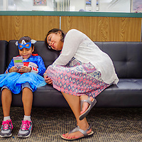 092714       Cable Hoover<br /> <br /> Karen Johnson, left, sits with Kylie Montaño as she plays a game during the superhero party at the Octavia Fellin Public Library Children's Branch in Gallup Saturday.