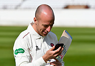 Jack Leach of Somerset looks at his phone during the 2019 media day at Somerset County Cricket Club at the Cooper Associates County Ground, Taunton, United Kingdom on 2 April 2019.