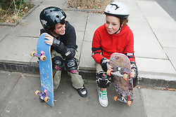 Young people sitting with skateboards.