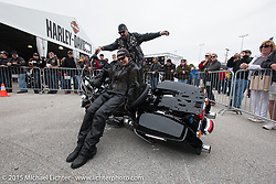 Jackie Wallace gets a little help from fellow New Yorker Jamie Frarey in picking up a bike that has fallen over at the Police Skills demo area of the Harley-Davidson display at Daytona International Speedway on the first day of Daytona Beach Bike Week 2015. FL, USA. Saturday, March 7, 2015.  Photography ©2015 Michael Lichter.