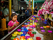 29 MAY 2018 - BANGKOK, THAILAND: A girl floats a candle in a water container during Vesak observances at Wat Hua Lamphong in Bangkok. Vesak is the Buddha's birthday, and one of the most important holy days in the Theravada Buddhist religion. Many Thais visit their local temples for Vesak and rededicate themselves to the Dharma, listen to talks about Buddhism and make merit by bringing flowers to the temple.       PHOTO BY JACK KURTZ