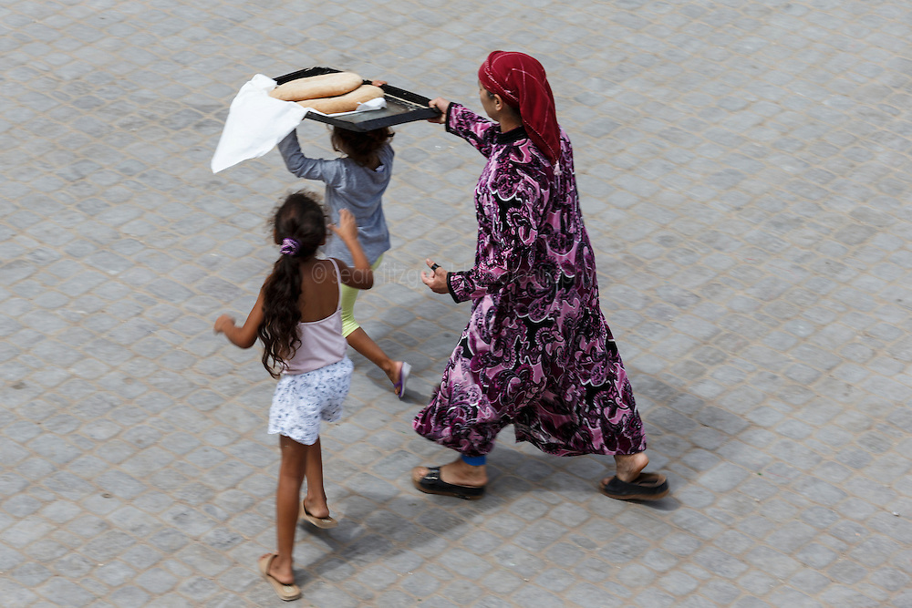 Girl carrying bread with help of family, El Jadida, Morocco.