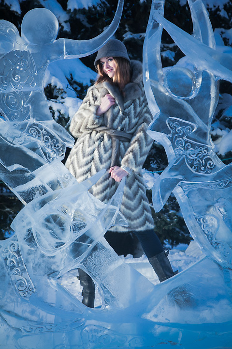 """Taylor Lee models a coat from Anchorage's """"Second Run"""" with the winning entry, """"Where We Dwell"""", ice sculpture by Jenny Rosenbaum and Paul Hanis during the """"Crystal Gallery of Ice"""" at Town Square, Anchorage, Alaska"""