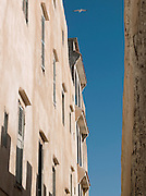 A narrow medina street sits between the buildings and the fortified wall in the coastal town of Essaouira, Morocco