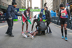 NYRR New York City Half Marathon: Mo Farah on ground after collapse after finish of race, race director Mary Wittenberg goes to help as top finishers Mutai, Sambu, Meb Keflezighi assist