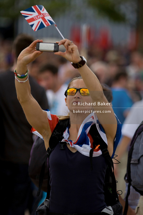 A Brit spectator photographs on a smartphone a crowded landscape in the Olympic Park park during the London 2012 Olympics. This land was transformed to become a 2.5 Sq Km sporting complex, once industrial businesses and now the venue of eight venues including the main arena, Aquatics Centre and Velodrome plus the athletes' Olympic Village. After the Olympics, the park is to be known as Queen Elizabeth Olympic Park.