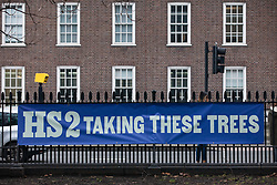 London, UK. 12th January, 2018. An anti-HS2 banner is hung from railings outside Euston station. Local residents and environmental campaigners are protesting against the planned felling of mature London Plane, Red Oak, Common Whitebeam, Common Lime and Wild Service trees in Euston Square Gardens to make way for temporary sites for construction vehicles and a displaced taxi rank as part of preparations for the HS2 high-speed rail line.