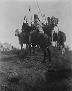 Four Crow men on horseback holding feathered spears, c1910. Photograph by Edward Curtis (1868-1952).
