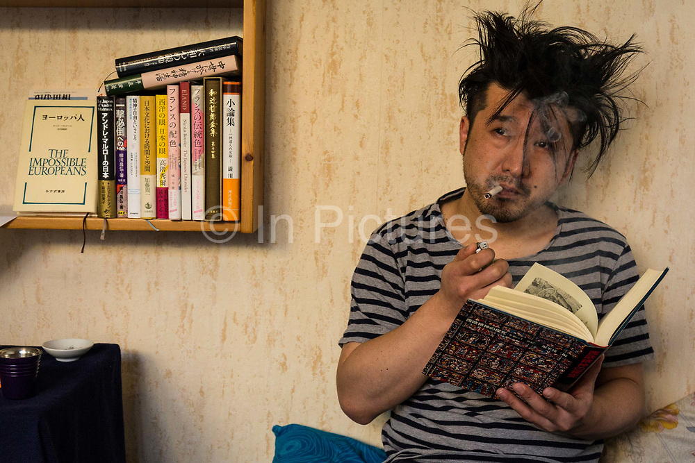 Masatsugu Okutani, 41 relaxes reading a book at home before getting ready for work, Paris.
