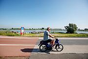 Bij Ameide rijdt een man op een snorscooter over de Lekdijk.<br /> <br /> Near Ameide a man rides his scooter.