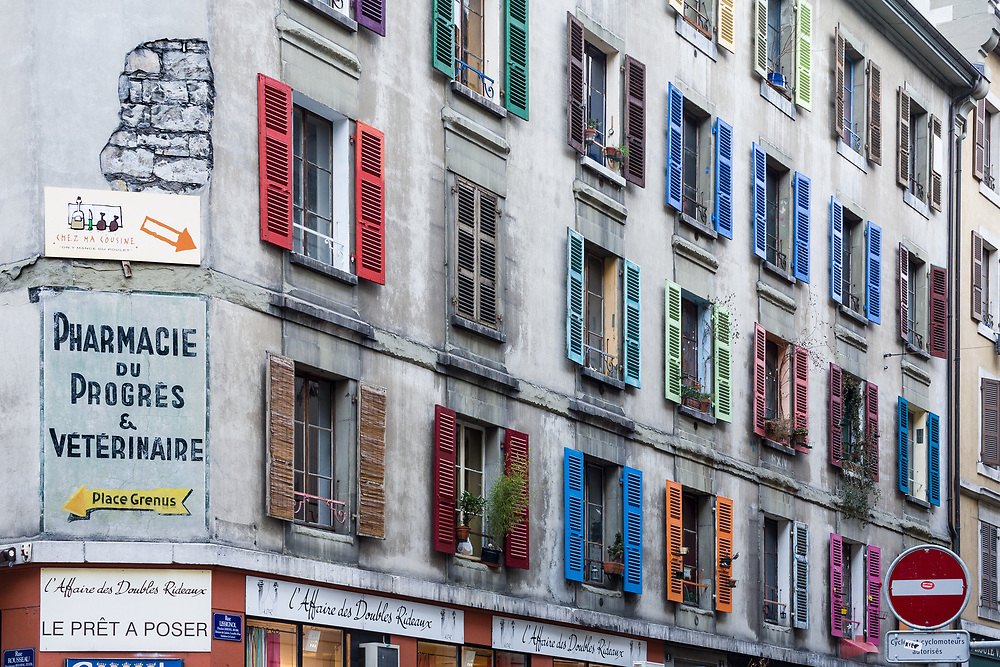 Multi Colored window shutters and signage adorn an old dreary tenement building with a little cheer in the Swiss city of Geneva.  Licensing and Open Edition Prints.