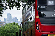 With the skyscrapers of the City of London, the capitals financial district, in the distance, a 33 London bus turns down Sydenham Hill, on 15th June 2021, in south London, England.