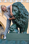 Saint Petersburg, Russia, 23/07/2005..A young woman poses on one of the stone lions in front of the Ministry of War headquarters.