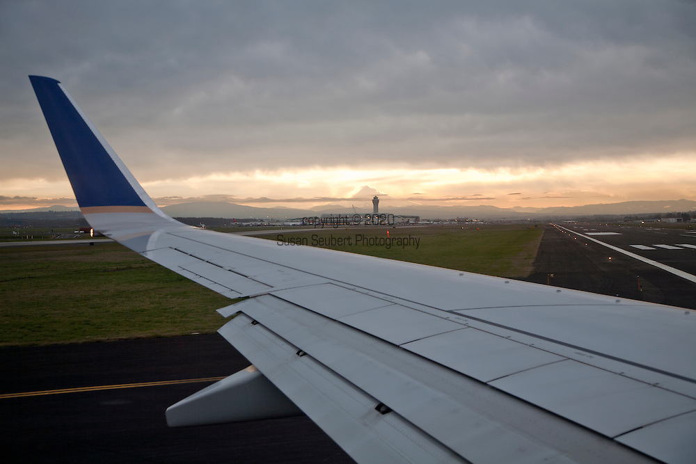 view from the window of an overwing airplane seat to the tarmac. Mt. Hood is visible in the distance as is the air traffic control tower as we taxi down the runway.
