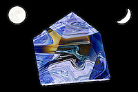 space crystal pyramid with blue and brown shades inside floating in black background with two moons.