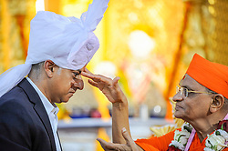 © Licensed to London News Pictures. 28/08/2016. London, UK. Sadiq Khan, Mayor of London, receives a tilak-chandlo from global spiritual leader Acharya Swamishree Maharaj and dons a Paag, a special turban reserved for leaders of the community, at Shree Swaminarayan Mandir, a Hindu temple in Kingsbury, north west London.  The Mayor was visiting the temple to thank the congregation for their prayers and blessings during his Mayoral campaign and to celebrate the second anniversary of the mandir. Photo credit : Stephen Chung/LNP