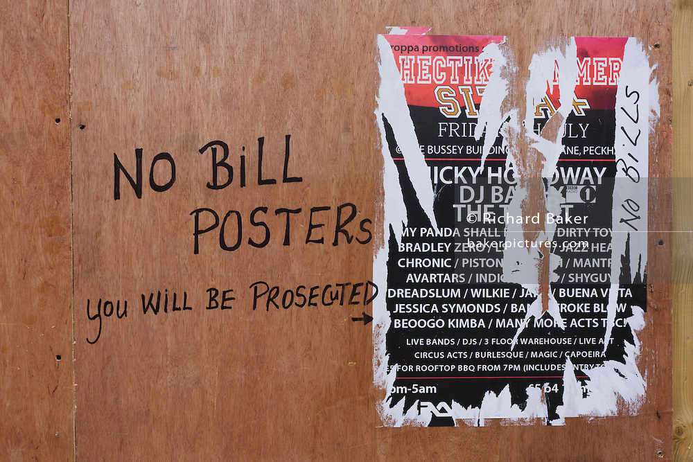 A No Bill Posters warning points to a torn poster stuck to a temporary construction site plyboard wall.