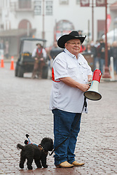 Announcer with his dog explaining history before Texas longhorns move along East Exchange Ave. during daily Fort Worth Herd Cattle Drive, Fort Worth Herd  Fort Worth Stockyards National Historic District, Fort Worth, Texas, USA.