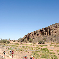 27 March 2007:  Participants run across the gorge of El Maharch during third stage of the 22nd Marathon des Sables between jebel El Oftal and jebel Zireg (20.07 miles). The Marathon des Sables is a 6 days and 151 miles endurance race with food self sufficiency across the Sahara Desert in Morocco. Each participant must carry his, or her, own backpack containing food, sleeping gear and other material.