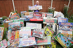 ** CAPTION CORRECTION Neil Scallan has spent an estimated £150,000 on monopoly boards, not £150,00 as stated in previous captions** © Licensed to London News Pictures. 24/07/2016. Crawley, UK.  Monopoly board game collector Neil Scallon with some of his 2200 unopened monopoly games, which he is hoping will set a Guinness World Record for the largest collection of Monopoly.  Scallan, who has been collecting for 10 years and estimates he has spent over £150,00 on the board games, is expected to set a  world record at the count later today (Sun) as the previous world record stands at around 500..  Photo credit: Grant Melton/LNP