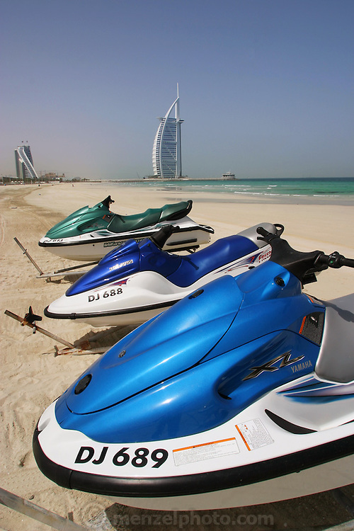 Jet skis on Jumeirah beach with the Burj-al-Arab luxery hotel in the background.  The Burj-al-Arab, built on an artificial island extending from the beach, is the world's tallest hotel. Dubai, United Arab Emirates.