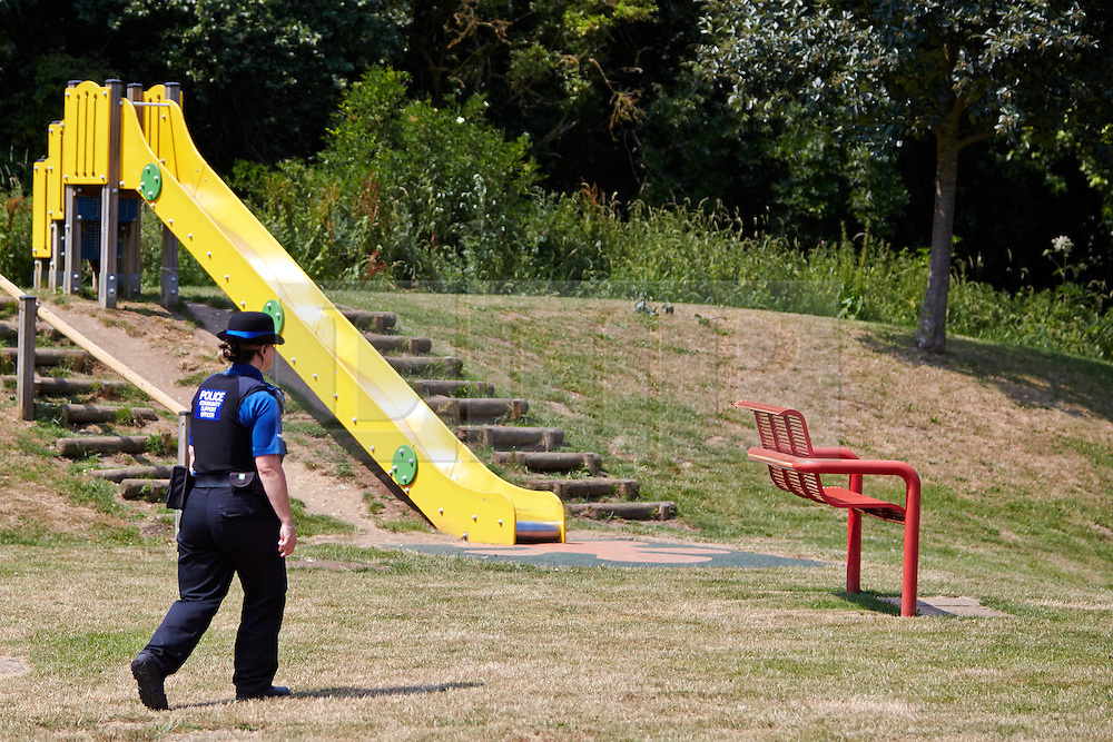 """© Licensed to London News Pictures.  18/07/2013. THAME, UK. A PCSO patrols a playground in Southern Road recreation ground in Thame, Oxfordshire where yesterday afternoon (Wed 17th) a 14-month old boy was hospitalised after picking up a discarded drugs wrap and chewing it. His condition is not thought to be serious but he was kept in overnight for observation.<br /> <br /> Police officers searched the scene for further paraphernalia and engaged with the council who will carry out additional cleaning at the recreation ground.<br /> <br /> Det Sgt Darren Cartwright of Thames Valley Police said: """"This was obviously a frightening experience for the boy's parents, but fortunately he doesn't seem to have been seriously harmed. It seems he had picked up a discarded paper wrap believed to have contained an illegal drug."""" <br /> <br /> Photo credit: Cliff Hide/LNP"""