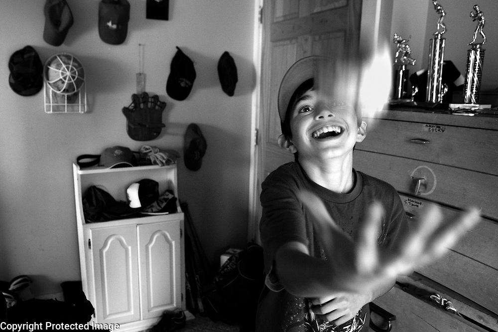 A boy plays with a baseball in his room in Peabody, MA.