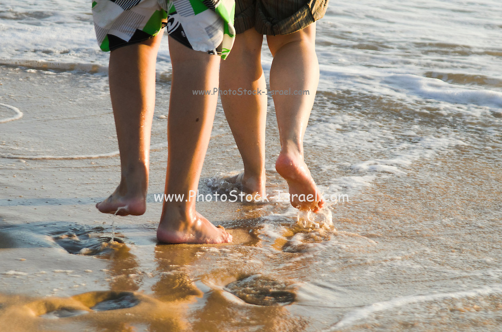 Feet of two youn teens playing on a beach