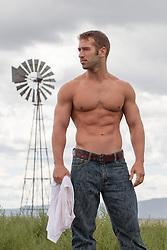 shirtless muscular man outdoors on a rural ranch