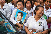 """04 FEBRUARY 2013 - PHNOM PENH, CAMBODIA: Cambodians stand near the National Museum with photos of former Cambodian King Norodom Sihanouk during his cremation service in Phnom Penh. Norodom Sihanouk (31 October 1922- 15 October 2012) was the King of Cambodia from 1941 to 1955 and again from 1993 to 2004. He was the effective ruler of Cambodia from 1953 to 1970. After his second abdication in 2004, he was given the honorific of """"The King-Father of Cambodia."""" Sihanouk died in Beijing, China, where he was receiving medical care, on Oct. 15, 2012.    PHOTO BY JACK KURTZ"""