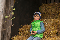 Little boy sitting on straw in the stable and smiling, Bavaria, Germany