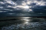 Sun breaks through dramatic clouds in the sky over Folkestone Harbour Arm during high tide from Sunny Sands Beach on 8th December 2018 in Folkestone, Kent, United Kingdom.