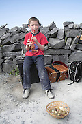 Young boy busking playing a tin whistle Inishmore, Aran islands, County Clare, Ireland
