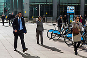 City workers walk past a Barclay's bike stand on the plaza outside Canary Wharf tube station, Docklands, London, United Kingdom.  Canary Wharf is the modern financial district of the city.