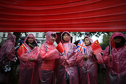 © Licensed to London News Pictures. 21/10/2015. London, UK. Supporters of Chinese President Xi Jinping wait in the rain opposite Downing Street. Photo credit: Peter Macdiarmid/LNP