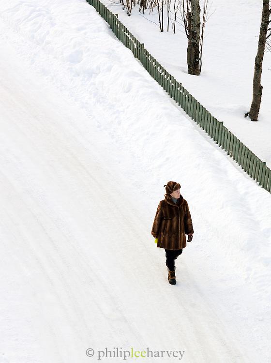 A woman walks down the frozen streets of Tromso, Norway