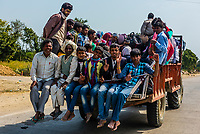 Local people riding on a the back of a truck during Holi Festival, Vrindavan, Uttar Pradesh, India.