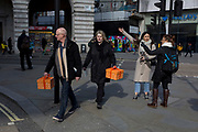 While two tourists discuss their direct of travel, two shoppers carry identical boxes tied with orange ribbons while passing through Piccadilly Circus and about to cross Regent Street, on 6th March 2020, in London, England.