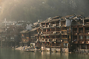 View of traditional old Chinese style stilted houses along a river in an old town, Fenghuang, Hunan Province, China