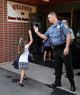 Mark Moglia, Delaware Valley School District police chief, greets a student at Delaware Valley Elementary School in Milford, Pa., on the first day of school, Monday, Aug. 30, 2010.