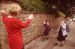 Mother standing in street waving two young daughters off to school,