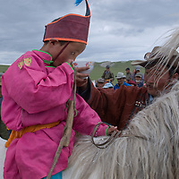 A father gives his costumed son a sip of ceremonial, fermented mare's milk after he rode to victory in a 20km race at a traditional naadam festival on a remote pass near Muren, Mongolia. A victory in these competitions brings great family pride and to increase his odds, the boy rode barefoot and bareback.